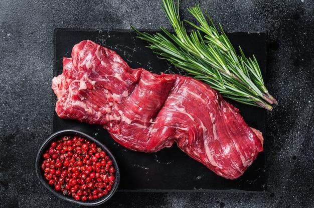 Bistecca di carne di manzo crudo gonna machete sul bordo di marmo