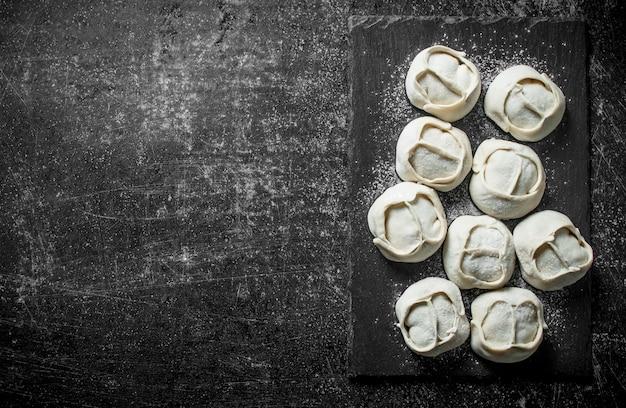 Gnocco di manta crudo con carne di manzo sul tavolo rustico scuro