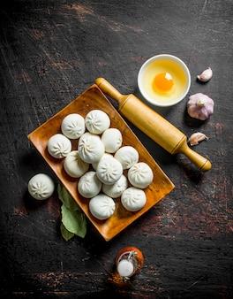 Gnocchi di manta crudi con uovo, aglio e foglia di alloro sul tavolo rustico scuro