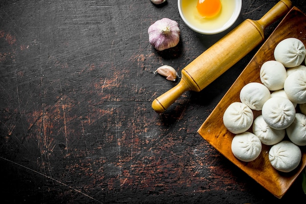 Gnocchi di manta crudi con aglio e uovo sul tavolo rustico scuro
