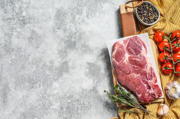 Bistecca di maiale in marmo crudo su un tagliere di legno. carne biologica. sfondo grigio. vista dall'alto. copia spazio.