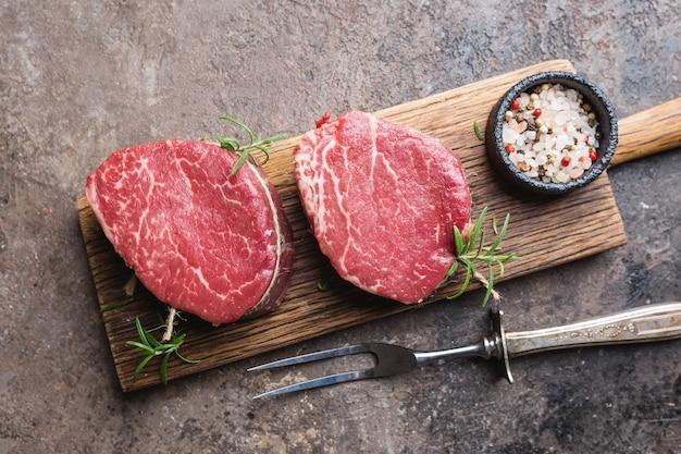 Bistecca di carne cruda marmorizzata filet mignon con condimenti su sfondo di pietra, vista dall'alto.