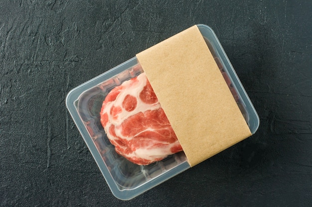 Bistecca di maiale marmorizzata cruda in confezione sottovuoto su sfondo nero, vista dall'alto, mockup del logo per il design