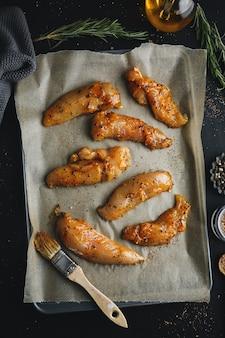 Petto di pollo marinato crudo su superficie scura con spezie pronte da cucinare