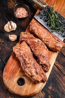 Bistecche di gonna marinate crude in salsa barbecue su un tagliere di legno con erbe aromatiche