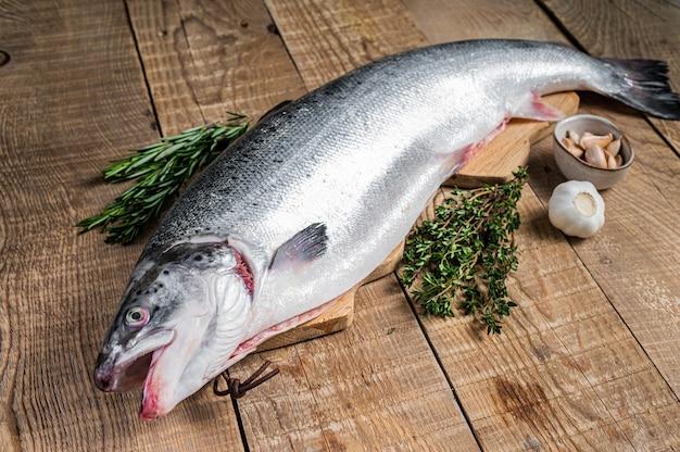 Pesce salmone marino crudo su un tavolo da cucina in legno con erbe aromatiche. fondo in legno.