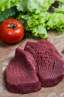 Barbecue della carne cruda con la superficie di legno degli ortaggi freschi. cibo, bistecca, barbecue di manzo, pomodori, peperoni, spezie per cucinare.
