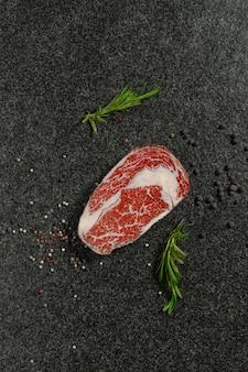 Carne cruda, bistecca di manzo con spezie su sfondo nero