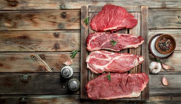 Carne cruda. bistecche di manzo e maiale con spezie. su un legno.