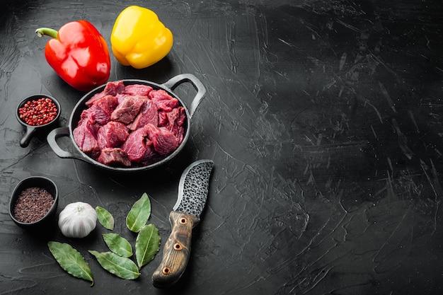 Carne cruda tagliata a dadini per stufato con peperone dolce in padella in ghisa