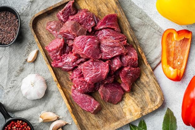 Carne cruda tagliata a dadini per stufato con peperone dolce, su sfondo di pietra grigia, vista dall'alto piatta