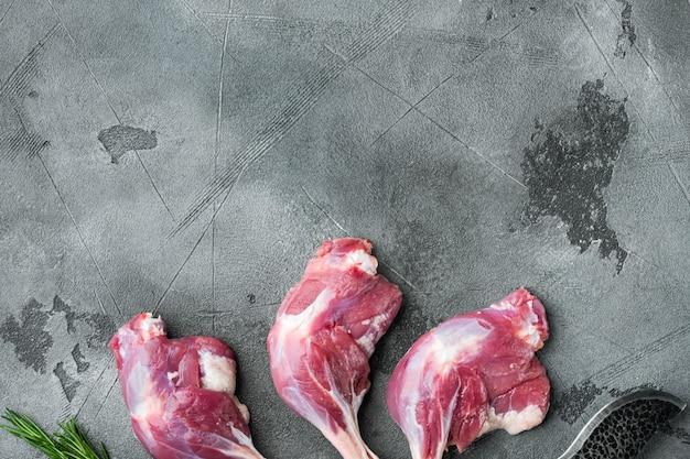 Carne cruda, cosce d'anatra incastonate, su pietra grigia