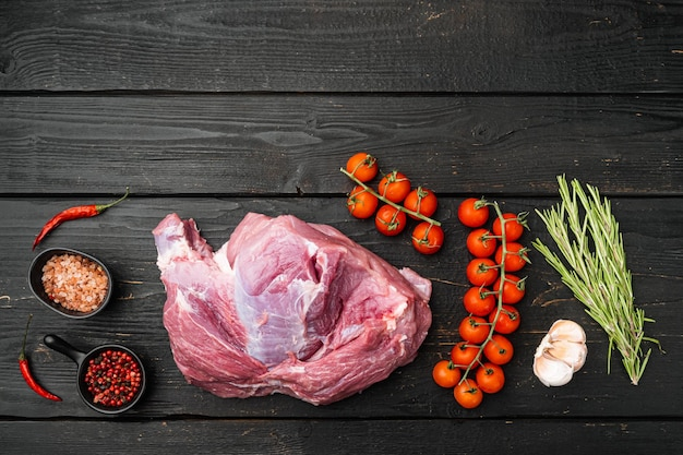 Carne cruda, pezzo di maiale con set di condimenti, su sfondo di tavolo in legno nero, vista dall'alto piatta, con spazio di copia per il testo