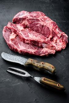 Bistecca di ribeye di carne cruda con set di condimento, con coltello e forchetta per carne, su pietra nera