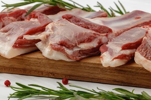 Costolette di carne cruda su tavola di legno su sfondo bianco