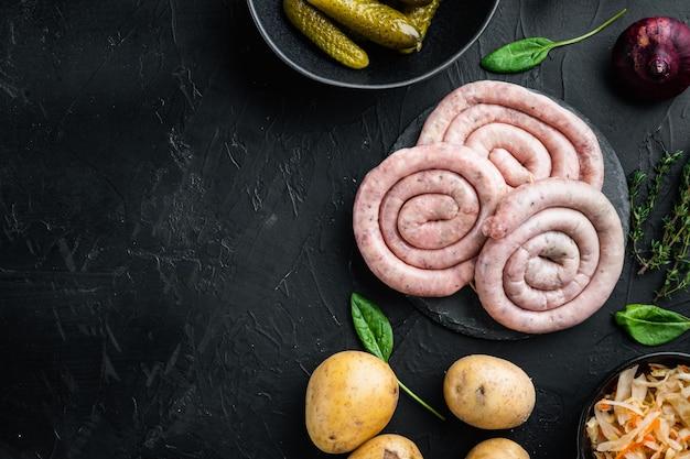 Set di salsiccia di carne cruda, su sfondo nero, vista dall'alto laici piatta, con spazio per il testo copyspace