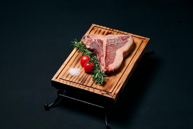 T-bone di bistecca della carne cruda sul nero.