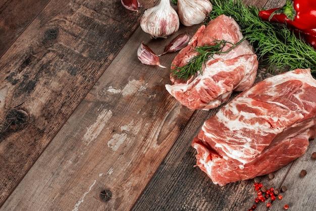 Carne cruda con verdure fresche e rosmarino e spezie sulla tavola di legno