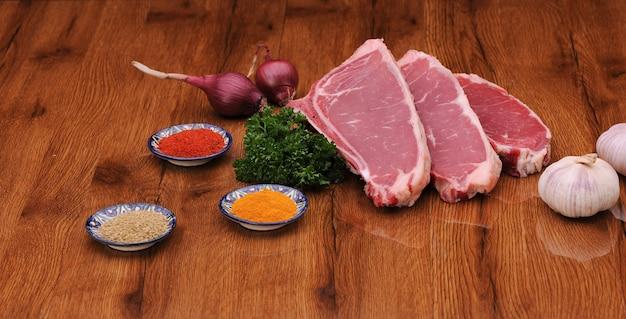 Carne cruda alle erbe e lattuga e cipolla con aglio su tavola verniciata