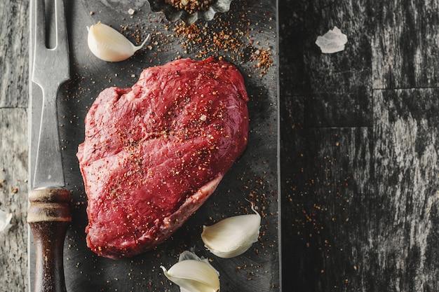 Carne cruda con spezie sul tavolo scuro. pronto per la cottura.