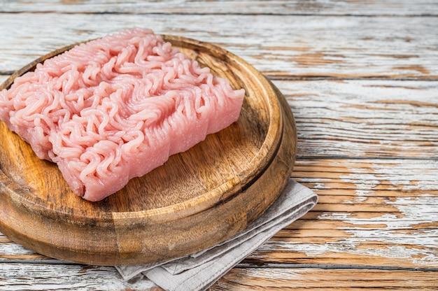 Tritare crudo o carne di pollo macinata su tavola di legno. sfondo bianco. vista dall'alto. copia spazio.