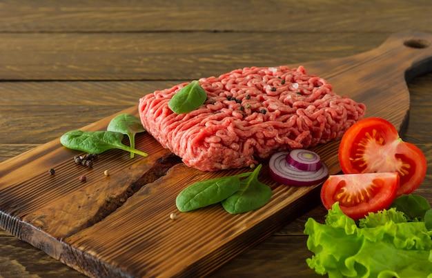 Carne di manzo macinata cruda su un tagliere di legno con verdure e spezie. cucinare e mangiare sano concetto.