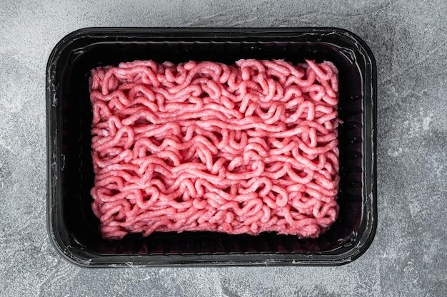 Carne macinata cruda in un contenitore di plastica nero su pietra grigia vista dall'alto laici piatta