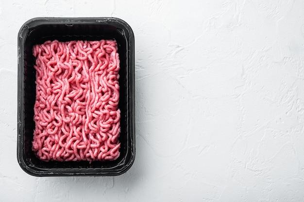 Carne macinata cruda in un contenitore di plastica nero, su bianco