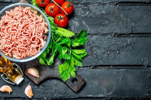 Carne macinata cruda in una ciotola con prezzemolo verde e pomodori.