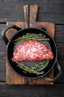 Cotolette di carne tritata cruda. set di hamburger di bistecca di maiale di manzo macinato fresco, in padella in ghisa, su sfondo di tavolo in legno nero, vista dall'alto piatta