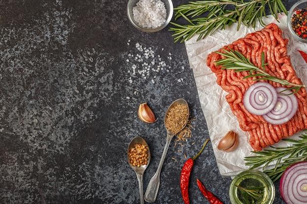 Carne macinata cruda su carta con cipolla, erbe e condimenti su bla