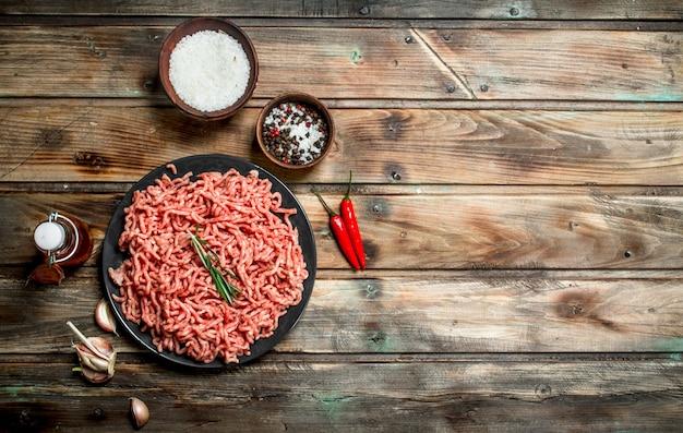Carne macinata cruda in un piatto con spezie ed erbe aromatiche.