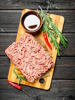 Carne cruda tritata con spezie ed erbe aromatiche. su uno sfondo di legno.