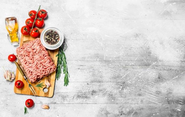 Carne cruda tritata con pomodori, rosmarino e spezie. su fondo rustico