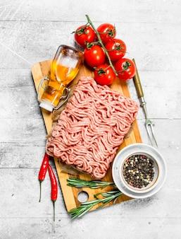 Carne macinata cruda con pomodori e spezie. su fondo rustico