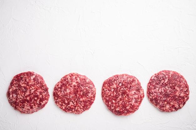 Hamburger di bistecca macinata cruda da set di carne di manzo, su sfondo di pietra bianca, vista dall'alto piatta, con spazio di copia per il testo