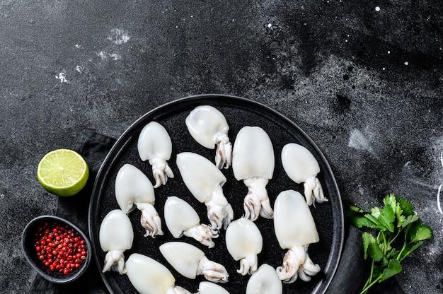 Mini seppie crude con rosmarino e prezzemolo su un piatto. superficie nera. vista dall'alto. copia spazio