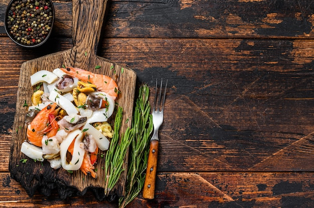 Cocktail di pesce crudo misto con gamberi, gamberi, cozze, calamari e polpo su un tagliere.