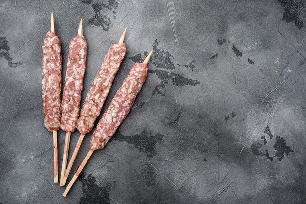 Set di spiedini di shish di kebab di montone crudo, su sfondo di tavolo in pietra grigia, vista dall'alto piatta, con spazio di copia per il testo