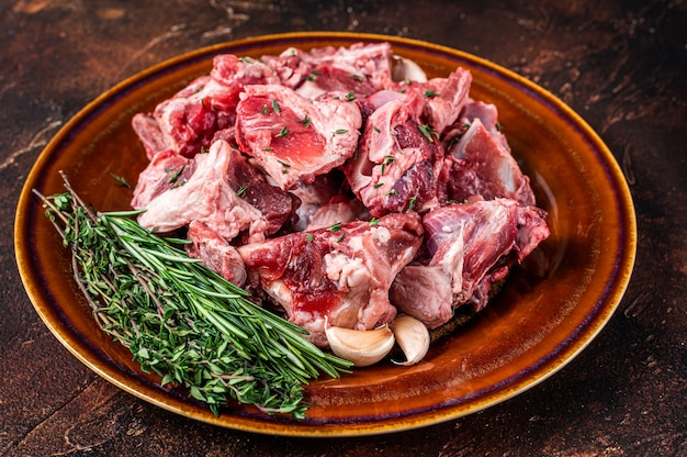 Carne di montone cruda tagliata a dadini per gulasch o stufato con osso su un piatto rustico. buio