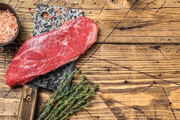 Bistecca di new york cruda su una mannaia, carne di manzo. fondo in legno. vista dall'alto. copia spazio.