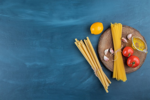 Tagliatelle crude con pomodori rossi freschi e olio su sfondo blu scuro.