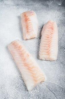 Filetto di merluzzo norvegese crudo sul tavolo da cucina. sfondo bianco. vista dall'alto.