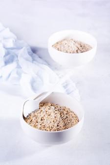 Farina d'avena cruda per fare una sana colazione in una ciotola di ceramica bianca