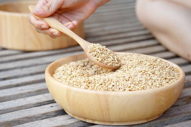 Farina d'avena cruda in un cucchiaio tenuto da una mano di donna con una ciotola di legno piena di avena sotto. il concetto di uno stile di vita sano, concetto di cibo vegano.