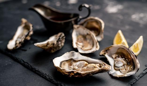 Ostriche aperte crude servite con limone e salsa su un piatto nero