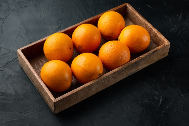 Set di arance cara navel biologiche crude, in scatola di legno, sul tavolo di pietra nera