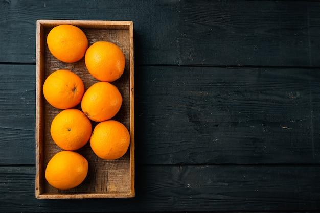 Set di arance cara navel organiche crude, in una scatola di legno, sul tavolo di legno nero, vista dall'alto laici piatta