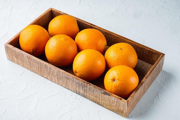 Set di arance cara navel biologiche crude, in scatola di legno, sul tavolo di pietra bianca