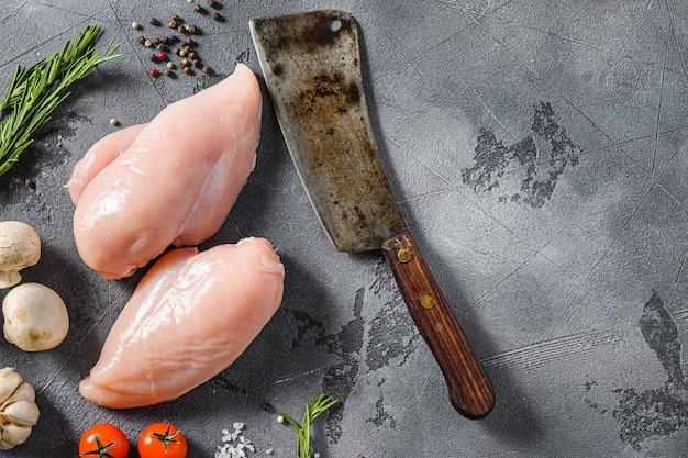 Petto di pollo biologico crudo con mannaia da macellaio di carne su sfondo grigio